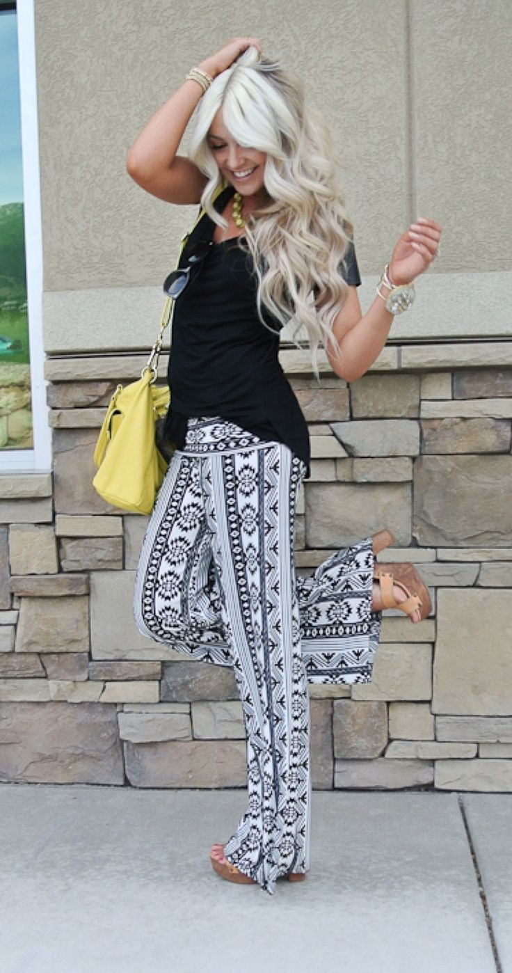 Black and white printed pants, black top, nude heels or wedges, and bright colored purse.