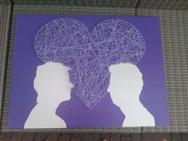 Silhouetten van een stel op een houtenplaat. Omringt door hartvormig spijkerpatroon
