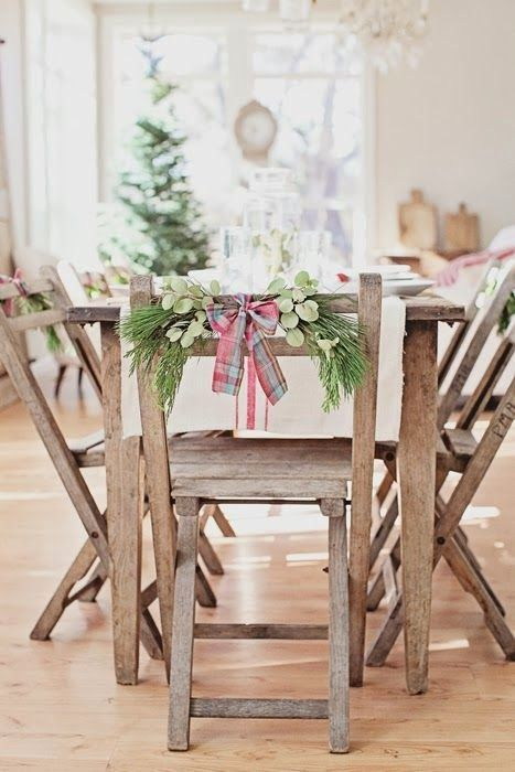 Cute Rustic Christmas Idea for the Dining Room: tie sprigs of greenery to chair-backs with ribbon.