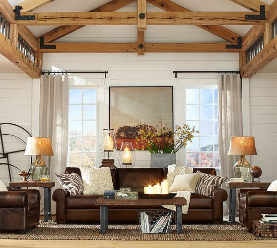 masculine leather sofas + cable knit and animal print pillows + neutral rug + wood coffee table + wood beams on the ceiling