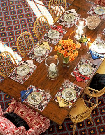 dining table - Place mats, flatware, and hurricanes from Ralph Lauren. Reproduction Windsor chairs from Nantucket House Antiques are mixed with a wing chair upholstered in Lee Jofa's Fairground Weave.  Read more: http://www.housebeautiful.com/decorating/sun-valley-barn-style-house#ixzz2lgmwiTOE