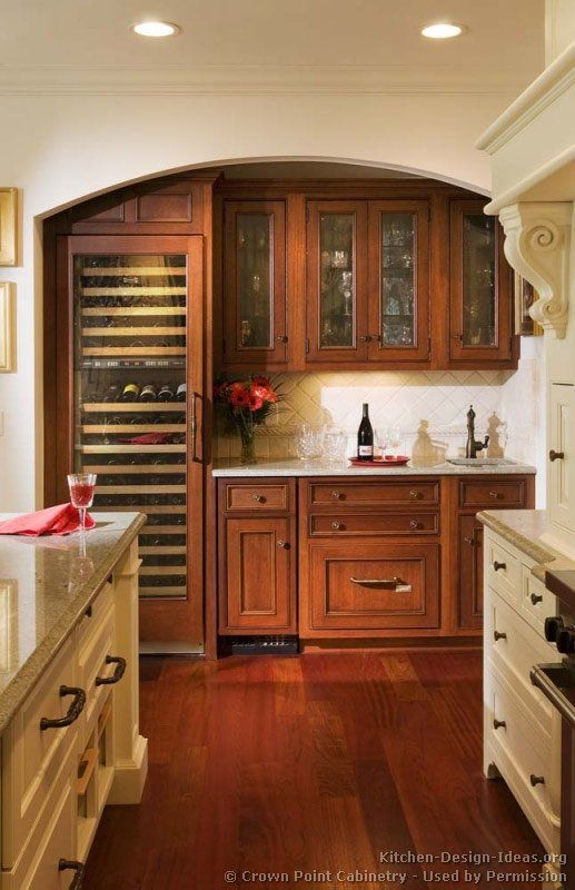 A luxury wet bar with mahogany cabinets, a tall glass-front wine cooler, and a panelized ice maker & dishwasher drawer. Victorian kitchens. (By Crown Point Cabinetry)