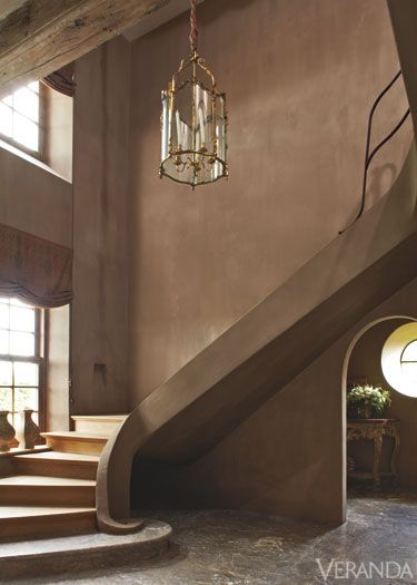 wall color & raise plaster for higher rail / Warm and Sophisticated. This entrance hall's sculptural cement and oak staircase is finished in a warm gray-brown chalk plaster.