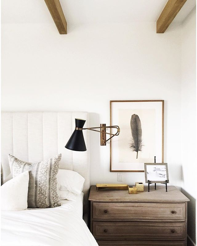 I love how the feather art, bed frame and wall sconce are layered compliments in the guest three a...