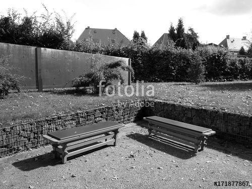 Rechtwinklig angeordnete Parkbänke in einem Park in Oelde bei Warendorf im Münsterland, fotografiert in klassischem Schwarzweiss