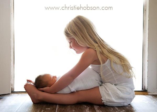 cute newborn sibling pose
