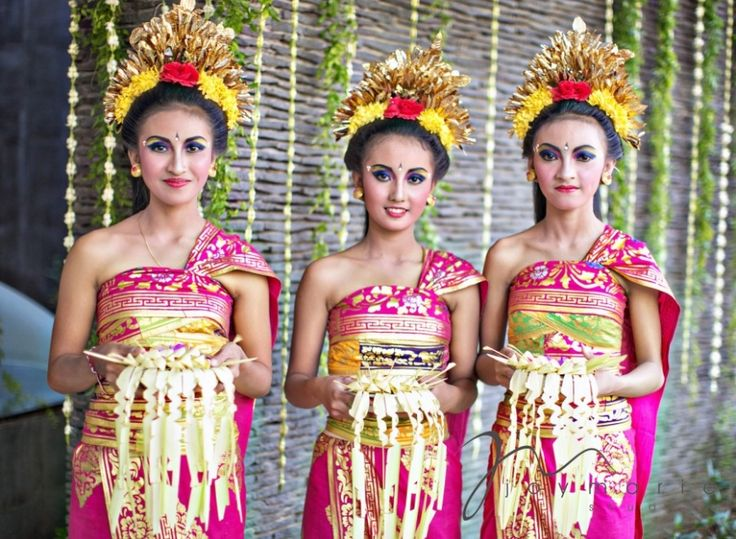 Balinese girls greeting wedding guests in traditional dress. Photo by Joy Marie Studios.