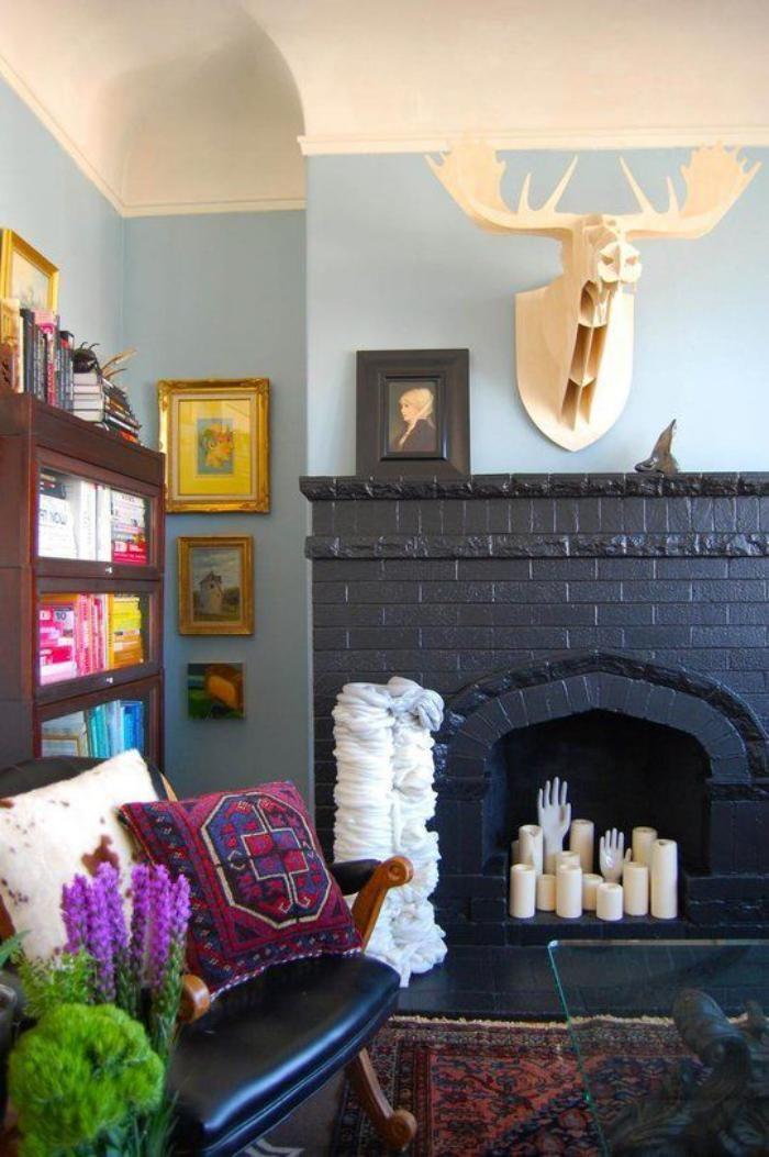 manteau de cheminée noir et sculptures extravagantes, chaise en bois et cuir, coussin et tapis éthniques
