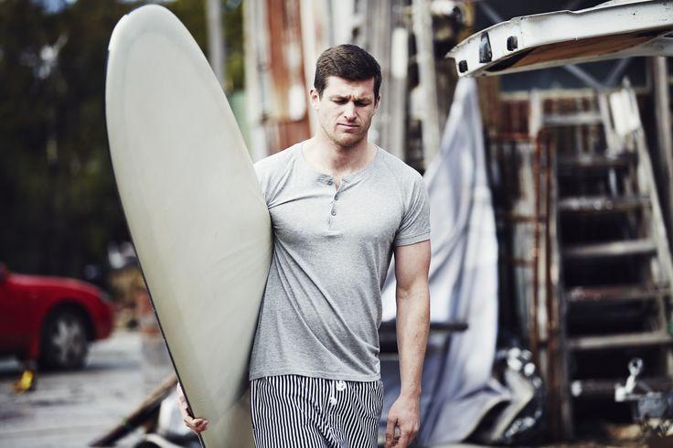 Scott wears Lamrock Henley Tee In Grey Marle | Penkivil Shorts In Stripe. #campbellandhall #mensclothing #surfboard