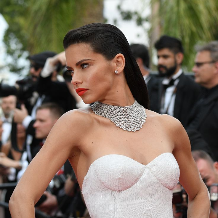Model Adriana Lima, renowned as a Victoria's Secret Angel, wore a white sweetheart dress at the premiere of Loveless at Cannes, and chose a high voltage diamond bib by Chopard with a red lipstick and glossed back black hair. For glamour celebrity fashion Cannes Film Festival red carpet jewellery spotting travel here: http://www.thejewelleryeditor.com/jewellery/top-5/cannes-film-festival-red-carpet-jewellery-day-two/ #jewelry