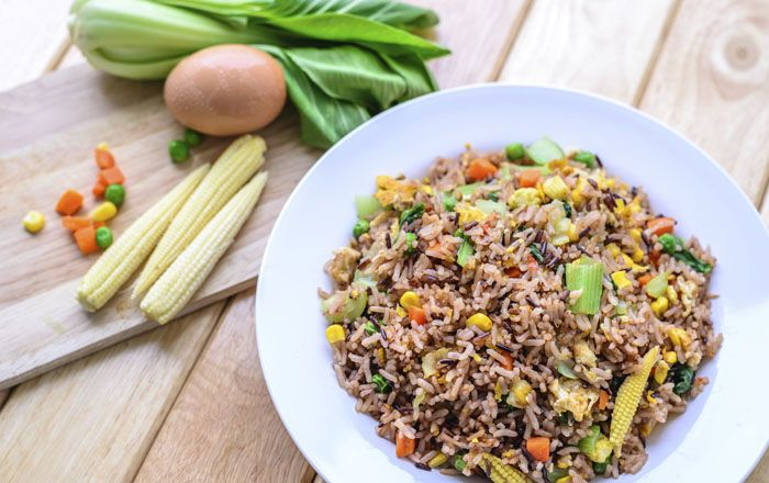 Fried rice with eggs and vegetables on white dish.