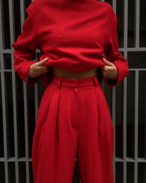 All bright red. An outfit with focus on the narrow waist. High waisted trousers with accentuated waist and volume around the hips and a red jumper on top.