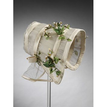 Wedding bonnet by an unknown British designer made in 1845, cream silk tulle bonnet trimmed with sprays of imitation orange blossoms...