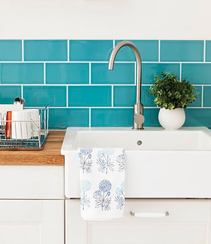 Add a pop of colour to a neutral kitchen with a bright aqua splash back. Photography: Oliver Gordon. Find more kitchen ideas at housebeautiful.co.uk