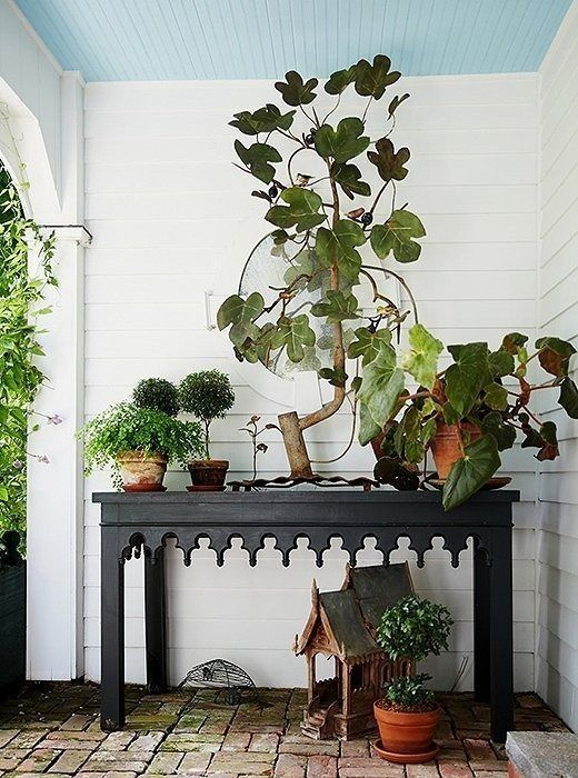 When arranging plants on an outdoor console table, group varying heights and types in odd numbers—and don't be afraid of overdoing it!