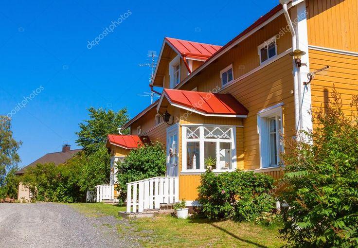 Trä gult radhus med rött tak och vita Fönstren i skandinavisk stil