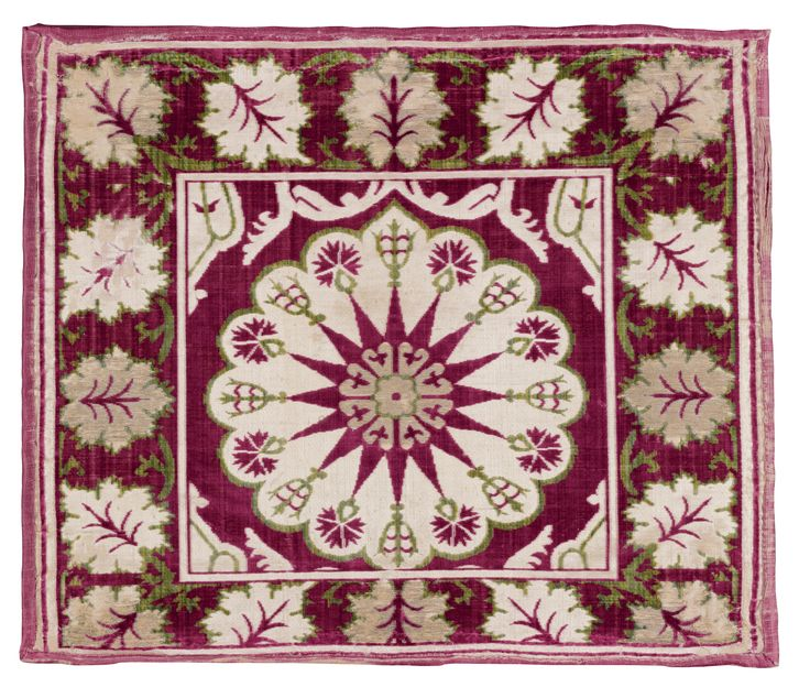 velvet` yastik', Bursa or Istanbul, Ottoman  of rectangular format, the central square with a floral roundel enclosing a flowerhead and star, with alternating tulip and carnations, with elements of further design around edges, within a four-sided border with scrolling leaf design, now mounted on later stretcher      Approximately 58 by 68cm., 1ft. 11in., 2ft. 2in.  17th century
