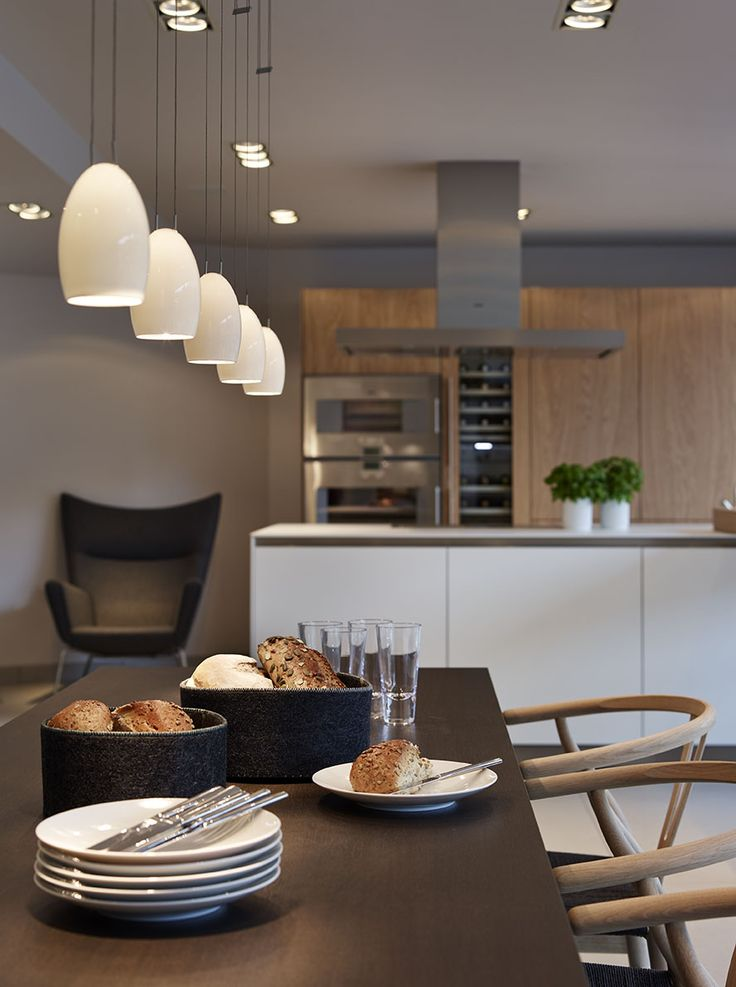A bulthaup b3 'Rough Sawn Oak' kitchen, a bulthaup C3 wall-hung bench and dining table and Carl Hansen 'Wishbone' chairs. Gaggenau appliances are featured throughout and Tobias Grau lighting completes the display. #kitchens #b3