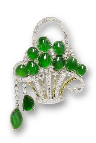 A jadeite and diamond giardinetto brooch The openwork brilliant-cut diamond basket, filled with jadeite cabochons of intense emerald green colour and of good translucency, suspending two tassels of diamonds and jadeite, mounted in 18k white and yellow gold.