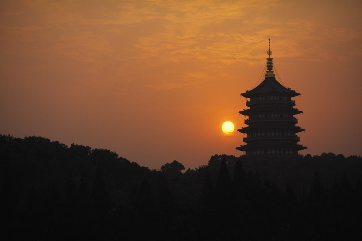 A sunset you've gotta see in your lifetime: the glowing sun dips behind a pagoda at @Mandy Dewey Seasons Hotel Hangzhou at West Lake.