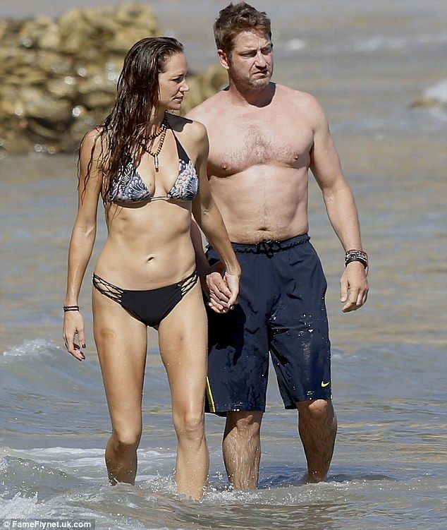 Beach bums: Gerard Butler and girlfriend Morgan Brown had a ball in the surf in Malibu on ...