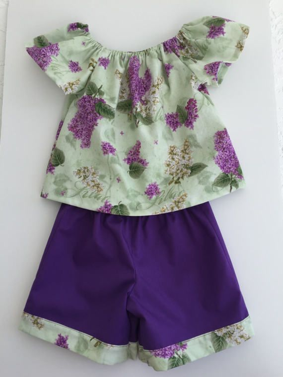 With spring and summer right around the corner. this two-piece shorts and flutter sleeve peasant top set makes a perfect addition for a toddlers warm weather wardrobe. The top is made from a quilters quality cotton with a lilac floral print. The shorts are a solid purple cotton with a band to match the top. All seams are serged to prevent fraying.   The set is made in my smoke-free, pet-free home.   Shipping to domestic US address only by USPS Parcel Post.