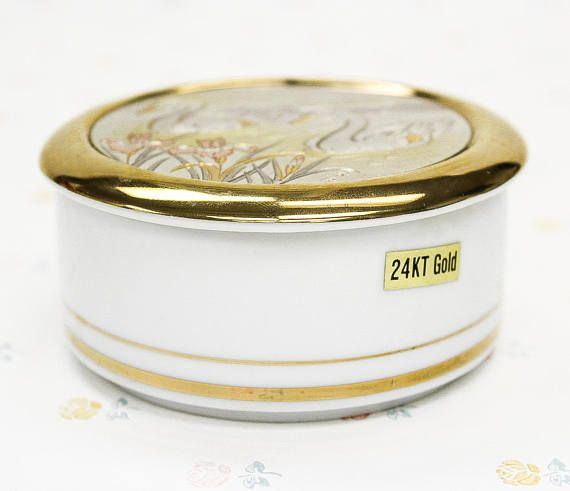 A beautiful porcelain trinket container with a gold lid that has an etching of two swans in a lake on the top. The white base has a double gold trim. There is a 24kt gold sticker present, as well as a Japan label on the bottom that is slightly damaged. Condition: Excellent condition!