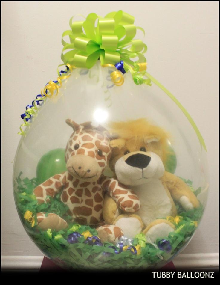 Centro de mesa para temática de la selva en globo burbuja con peluches de jirafa y león. #DecoracionBabyShower