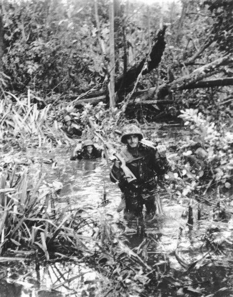 W.W. II, Jan 1944, Marines carry their weapons and ammunition overhead as they wade through a wetland area at Cape Gloucester