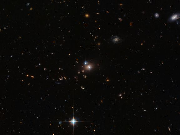 "These cosmic doppelgangers make up a double quasar known as QSO 0957+561, also known as the ""Twin Quasar"", which lies just under 14 billion light-years from Earth. Quasars are the intensely powerful centers of distant galaxies. This image was released Jan. 20, 2014."