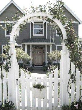 Gateway arbor, w/ fresh flowers pot. Nice way to frame the entry.