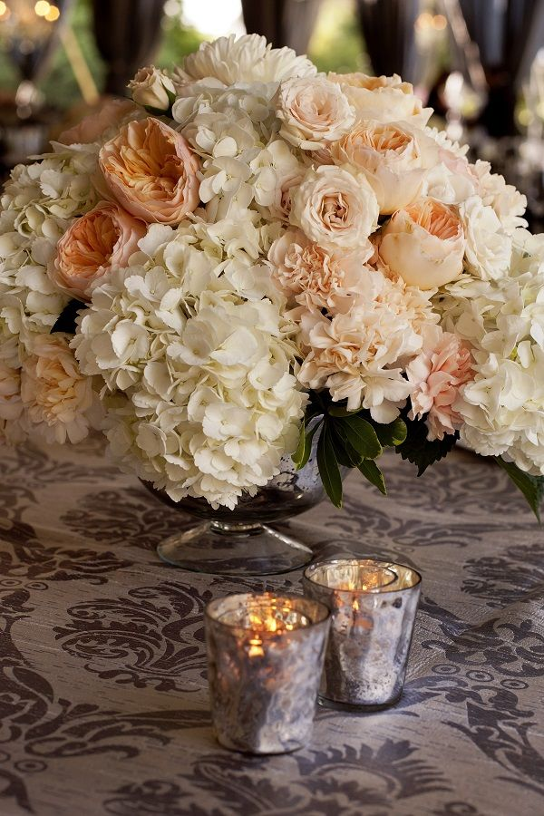 Low and lush wedding centerpiece in a footed mercury glass bowl. A feminine design with white hydrangea, peach garden roses, blush spray roses, dahlias, mums, carnations, and greenery for texture. Florals by freshdesign. Photography – Front Room Photography.