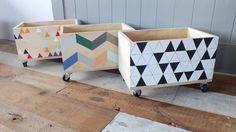 Bacs en bois joliment peints et montés sur roulettes pour faire du rangement.