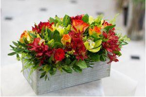 Σύνθεση σε κίτρινες, πορτοκαλί και κόκκινες αποχρώσεις, με τριαντάφυλλα και ορχιδέες σιμπίντιουμ.