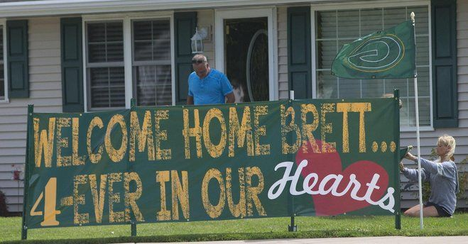 People erect signage welcoming back Brett Favre at a house across the street from Lambeau Field. Favre had his number retired and was inducted into the Packers Hall of Fame.