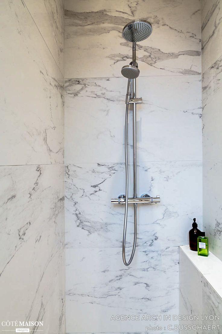 Une salle de bains épurée, avec un carrelage mural marbré.