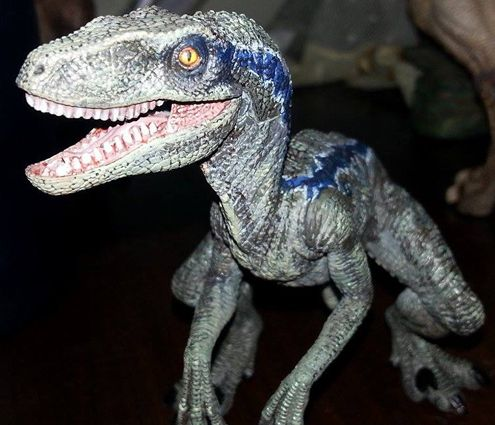 a blue dinosaur a papo velociraptor painted to look a dinosaur from the
