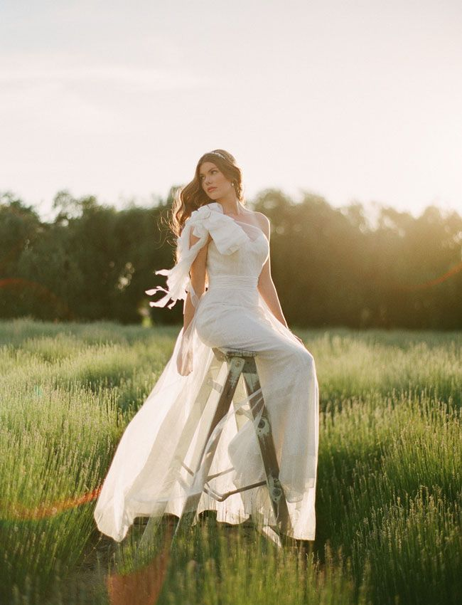 {Ruche Fall Bridal Collection + Win Dresses for Your Bridesmaids!}    Great photograph overall. The light and wind in her dress, the flowing hair and ribbon, the pose and posing of model, and the overall feel of the image. Plus, I would not have thought of a ladder as an option for this shoot, but it matches the rustic aspect well and I like how the model chose to sit on it.