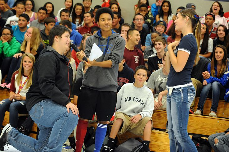 Ninth grader Brandon Mingee, 15, asks 12th grader Becca Mitchell, 17, to join him at their school's homecoming football game during an assembly Sept. 13 at Sand Creek High School in Falcon School District 49. The two were paired after 12th grader Lino Alvarez, 17, asked the school's freshmen who needed a date. Alvarez of the Psyco Scorps, a school pride group, requested someone from the senior class to join Mingee.
