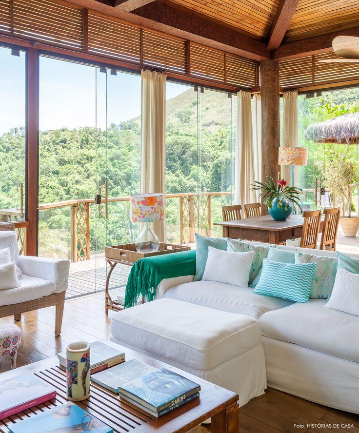 Sofá branco, estampas em cores pastel, móveis de madeira e fibra natural na decoração dessa casa em Ilhabela.