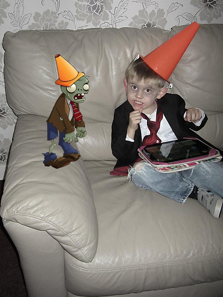 Plants vs Zombies kid costume - Kind verkleed als Plants vs Zombies kegel zombie. Nodig; kleine oranje pilon, wit overhemd, rode stropdas, colbertje, kapotte spijkerbroek. Gezicht wit schminken met zwarte wallen. Leuke outfit voor Halloween.