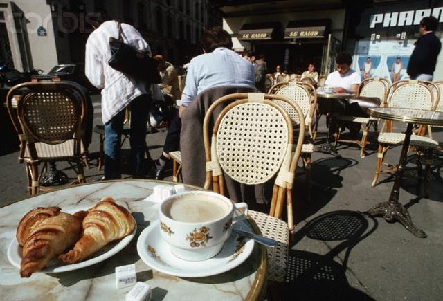 café et des croissants à une table en plein air à Paris