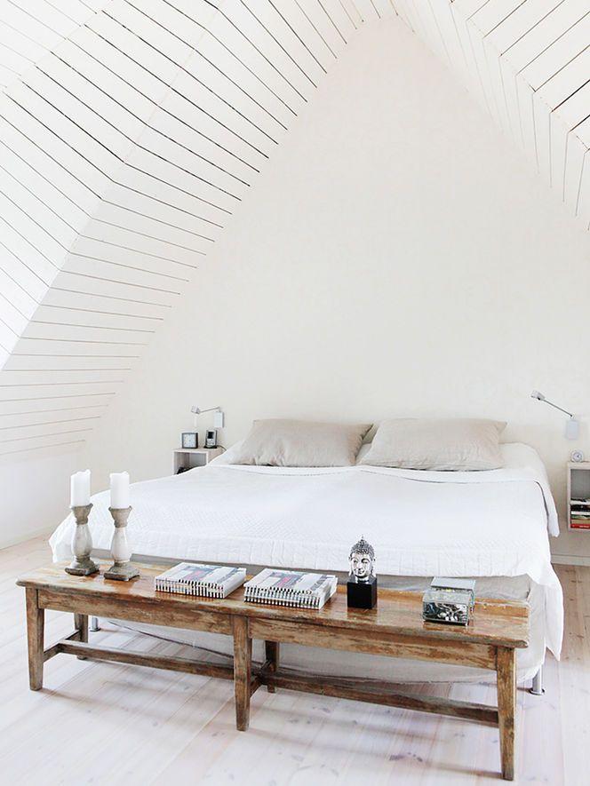 Quarto branco com teto inclinado