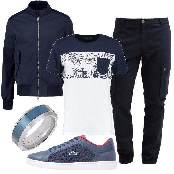L'outfit è composto da un bomber leggero blu navy con chiusura con zip, una t-shirt con stampa ed un paio di pantaloni cargo. Il look si completa con un paio di sneakers basse Lacoste ed un anello a fascia in acciaio inossidabile.