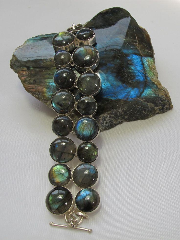 "Sixteen richly reflective round polished cabachon Labradorite gemstones in hand-matched graduated sizes, bezel-set in 925-hallmarked sterling silver, with adjustable toggle clasp. Length: 6-8""+ Widest"