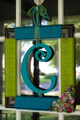 Get an old frame, wrap yarn around it, add a painted wooden letter in center, and embellish with fabric flowers.  SO CUTE!
