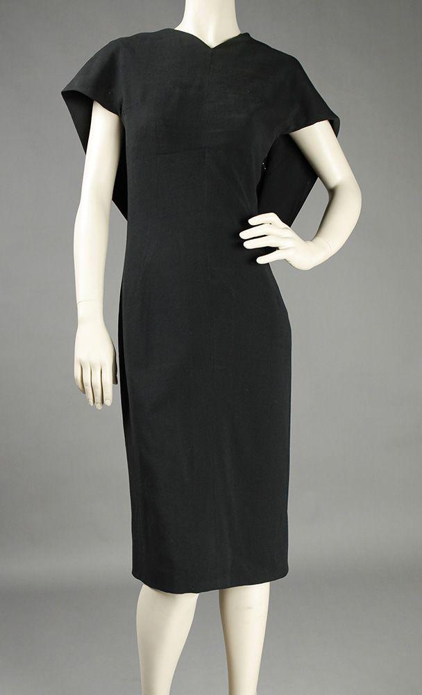 Traje de cóctel PERTEGAZ.  De color negro, con falda a la rodilla, presenta un original corte ceñido en el frente, con escote cerrado, en pico, que cae hacia atrás cubriendo los hombros, y formando un amplio pliegue decorativo en la espalda.  Talla 40-42 aprox.