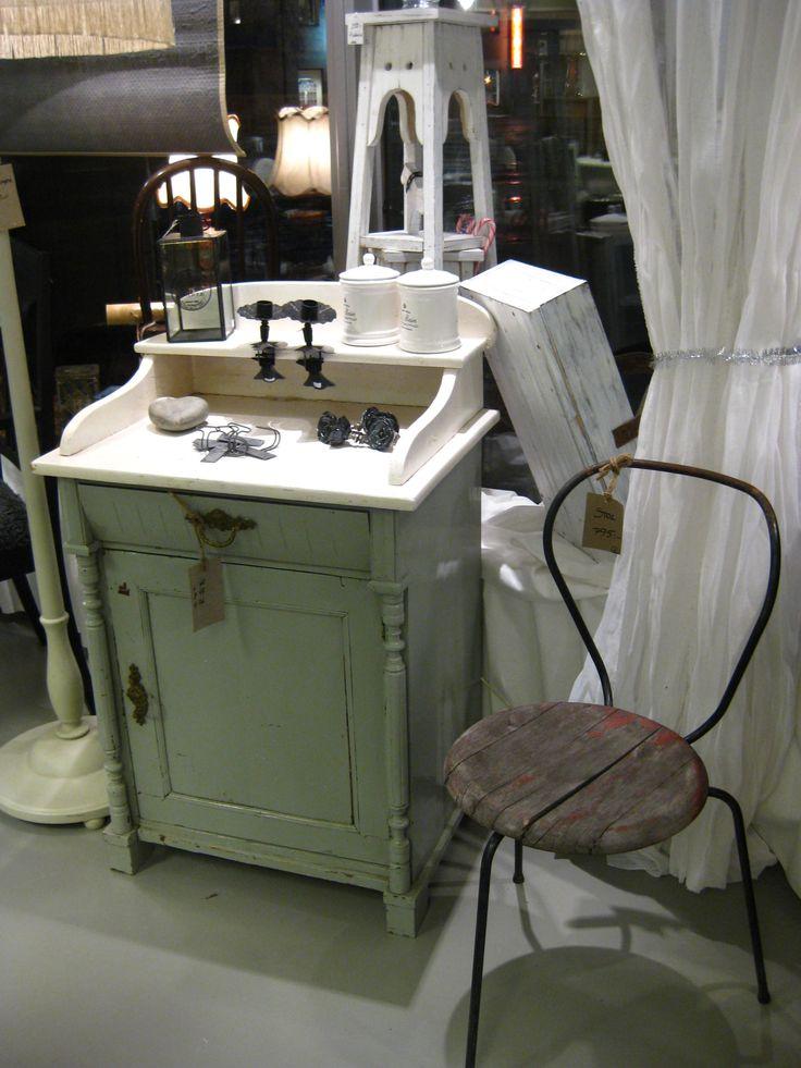 En fin gammal kommod i varmgrå nyans med vit skiva