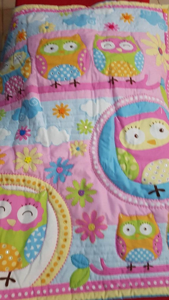 A beautiful embellished Owl quilt or toddler bed patchwork quilt we have called Taylah  Pastel pinks, lemons,blues, perfect for little princesses.  Cot quilt measures 74 cm wide by 93 cm long which fits most cots or toddler beds.  Embellished with rhinestones (adhered not sewn) buttons and hand quilting to emphasis shapes. please bare in mind embellishments are not suitable for very young children  Polyester wadding is perfect for those with allergies. Cotton panel and cotton backing…