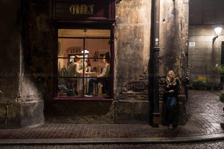A woman smokes a cigarette outside of a restaurant, Krakow